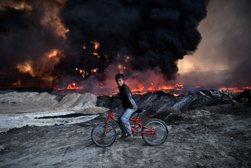 When IS set fire to oilfields surrounding Mosul, the sky darkened, and images from the siege of the city took on an apocalyptic hue. In this image, the juxtaposition with the youngster on his bright red bike creates a bizarre yet compelling tableau. One tiny, brief moment that has little directly to do with the story of the conflict, and yet captures its essence entirely.
