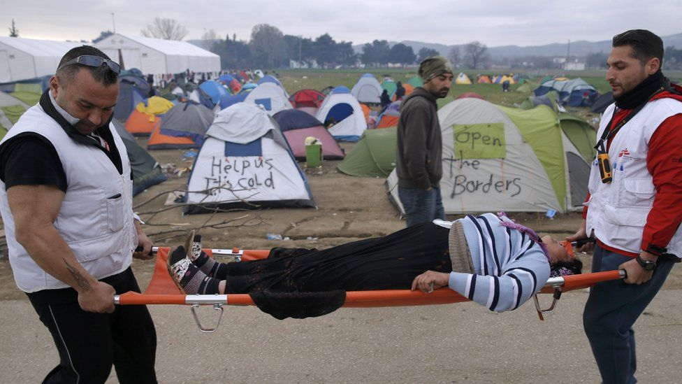 Medical volunteers carry a woman on a stretcher after she collapsed at the Idomeni camp (07 March 2016)
