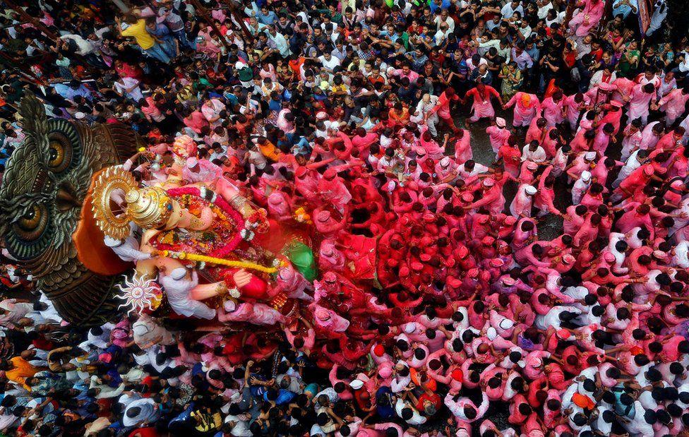 Devotos cargan el ídolo del dios hindú Ganesh, el dios de la prosperidad, por las calles en el último de los 10 días de duración del festival de Ganesh Chaturthi en Mumbai, India.