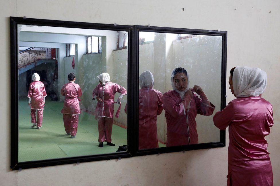 Hatifa Rezai , una de las estudiantes, se alista frente a un espejo ajustándose el uniforme.