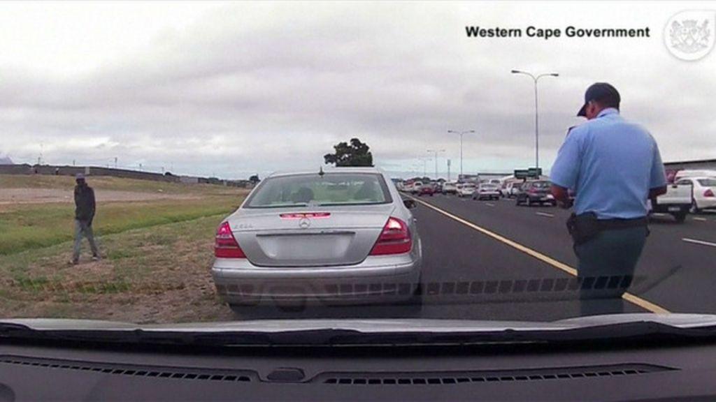 Policial é alvejado diante de câmera, mas volta para multar ...