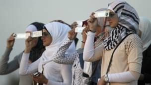 Mujeres aprecian el eclipse