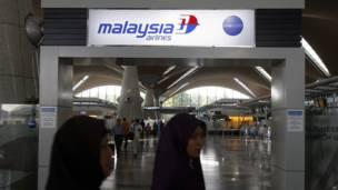 Các hành khách đi qua một biển hiệu của Hàng không Malaysia.