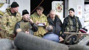 Un clérigo se dirige a los manifestantes prorrusos durante un mitin en la entrada de la oficina de la sede Servicio de Seguridad de Ucrania (SBU), en Luhansk, donde se levantó una barricada.