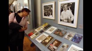 Una mujer mira libros y artículos del autor en Colombia.