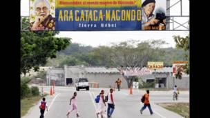 """Gente bajo una pancarta en la que se lee """"Bienvenidos a Macondo""""."""