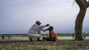 Un père coupe les cheveux de son fils à Melut sur les rives du Nil, Soudan du Sud