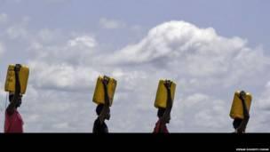 Des femmes portent des barils d'eau sur leur tête, Mingkaman , Etat de Lakes, Soudan du Sud