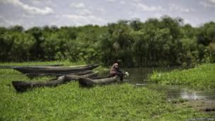 Un pécheur assis dans son canoë sur le Nil, Mingkaman, Soudan du Sud