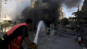 Bomberos palestinos intentan controlar un incendio.