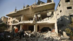 Palestinos de pie junto a escombros de una un edificio que según la policía fue destruido por un ataque aéreo israelíi