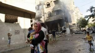 Mujer palestina corre con un niño en brazos tras lo que la policía dice que fue un ataque de Israel