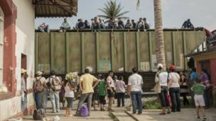 Migrantes sobre vagón de tren
