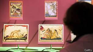 Mujer viendo exposición de ilustraciones del Kama sutra