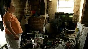Mujer mira su casa después del huracán.
