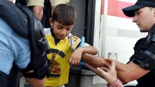 la policía croata ayuda a un niño migrante a bajarse de un tren