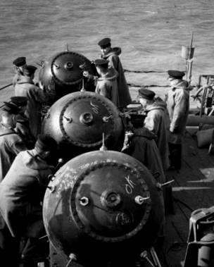 Efectivos de la Marina Real Británica colocan minas en posición para lanzarlas al agua.
