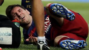 Messi tirado en el suelo mientras es atendido de su lesión.