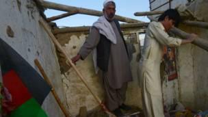أفغانيان يرفعان أثر الدمار.