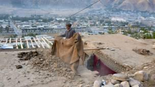 أفغاني يزيل الدمار فوق سقف منزله، أفغانستان.