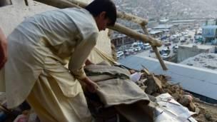 أفغاني يرفع الأنقاض عن سقف منزل