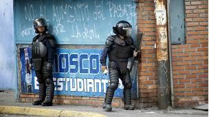 Dos policías se resguardan de las protestas en San Cristobal