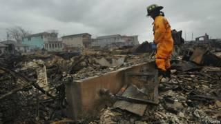 Un bombero recorre una zona de casas devastadas por el paso de la tormenta Sandy en el barrio de Queens, Nueva York