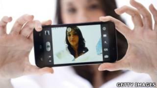 Joven tomándose una foto con su celular