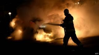 Bombero intenta apagar un coche en llamas en los suburbios de Estocolmo