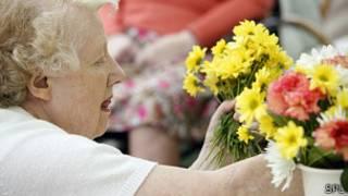 Mujer mayor arreglando plantas