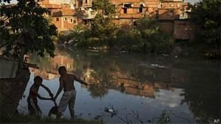 Crianças em um rio poluído no complexo de Manguinhos, Rio de Janeiro (AP)