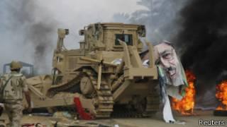 Un bulldozer militar blindado rompe un póster de Morsi