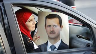 Simpatizante de presidente de Siria muestra un afiche en Damasco