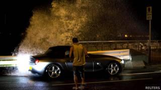 香港岛维多利亚港海旁一名男子在巨浪刷岸下试图返回他的汽车(22/9/2013)
