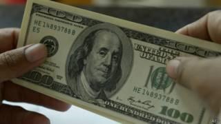 Una persona sostiene un billete de cien dólares estadounidenses