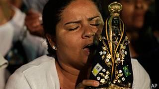 mujer reza con imagen de nuestra señora de aparecida, en brasil