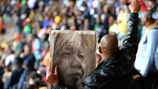 Hombre con un periódico con la imagen de Mandela