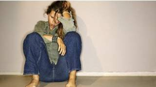 jovem sentada aparentando estar deprimida
