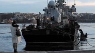 Mulher olha para navio ucraniano isolado na baía de Sevastopol (foto: AFP)