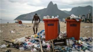 Playa de Ipanema con basura y el morro de los Dois Irmaos al fondo