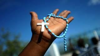 mujer sostiene un rosario