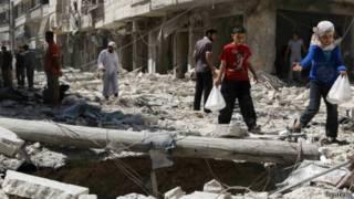 Niños evacúan un lugar atacado con bomba, en Siria