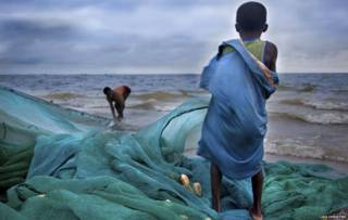 Niño con una red de pesca frente al mar