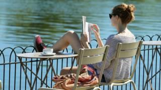 Una chica lee un libro en una terraza