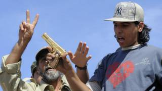 Mohammed Elbibi con la pistola de oro de Gadafi