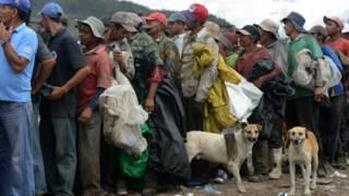 Personas que viven de recoger basura hacen cola para recibir alimentos de una ONG en Honduras