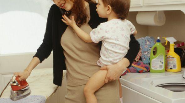 Mujer con niño planchando