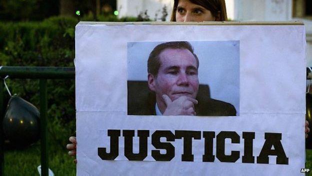 Una mujer sostiene una pancarta en reclamo de justicia por la muerte del fiscal en enero de 2015