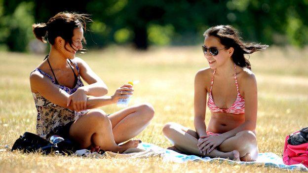Девушка наносит на кожу солнцезащитный крем