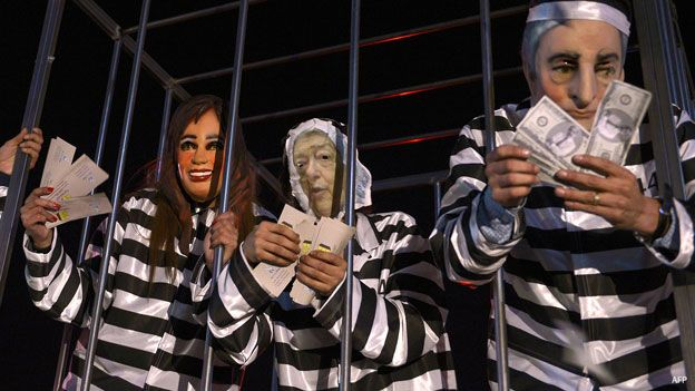 Personas vestidas como prisioneros con máscaras de Néstor y Cristina Kirchner.